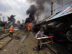 JAKARTA, INDONESIA - DECEMBER 09:  Emergency crews tackle the fire on the train wreck on December 9, 2013 on the outskirts Jakarta, Indonesia. A commuter train collided with a vehicle reportedly carrying liquefied gas canisters at around 11:20am local time. At least five people are reported dead.  (Photo by Nurcholis Anhari Lubis/Getty Images)