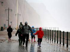 SIDMOUTH, UNITED KINGDOM - DECEMBER 23:  People brave the stormy weather and walk besides the beach on December 23, 2013 in Sidmouth, England.  The Met Office has issued a number of severe weather warnings for heavy rain and high winds and is warning that it may lead to some travel disruption as people travel for Christmas.  (Photo by Matt Cardy/Getty Images)
