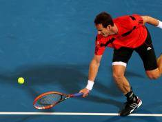 Andy Murray of Great Britain returns the ball to France's Jo-Wilfried Tsonga during their Mubadala World Tennis Championship match in the Emirati capital Abu Dhabi on December 26, 2013. AFP PHOTO/MARWAN NAAMANI        (Photo credit should read MARWAN NAAMANI/AFP/Getty Images)