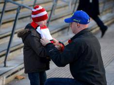 LONDON, ENGLAND - DECEMBER 08:  A man adjusts a boy's matchday scarf ahead of the Barclays Premier League match between Arsenal and Everton at Emirates Stadium on December 8, 2013 in London, England.  (Photo by Michael Regan/Getty Images)