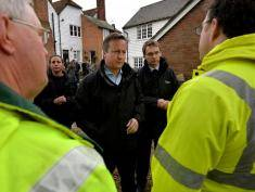 YALDING, ENGLAND - DECEMBER 27:  Britain's Prime Minister David Cameron (C) talks with residents and environment agency workers in the village of Yalding during a visit on December 27, 2013 in Yalding, England. Mr Cameron spoke to residents in the village in southeast England that was effected by flooding over the Christmas period. Some 50,000 homes in Britain were without power on Christmas Day following recent storms, while hundreds of people were evacuated due to flooding. (Photo by Ben Standsall WPA-Pool/Getty Images)