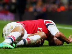 LONDON, ENGLAND - JANUARY 04:   (EDITORS NOTE: Retransmission of image #460558025 with an alternate crop) Theo Walcott of Arsenal lies injured on the pitch during the Budweiser FA Cup third round match between Arsenal and Tottenham Hotspur at Emirates Stadium on January 4, 2014 in London, England.  The injury sustained has led England and Arsenal forward Walcott to be ruled out for six months with an anterior cruciate ligament injury which will see him miss out on the 2014 World Cup.(Photo by Clive Rose/Getty Images)
