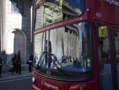 Pedestrians are seen reflected in a bus window as they pass the Bank of England (BOE) in the City of London, U.K., on Thursday, May 2, 2013. Bank of England policy maker Ben Broadbent said there are more reasons to be optimistic about the economy while acknowledging that there may be revisions to last week's better-than-forecast economic data. Photographer: Simon Dawson/Bloomberg via Getty Images