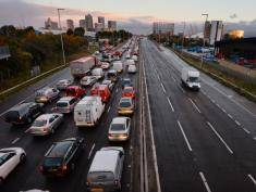 Traffic queues on a main route into London by the towers of London's financial district Canary Wharf (L) on October 28, 2013 after a strong storm causes travel disruption. Britain faced travel chaos on October 28 and over 200,000 homes were without power as one of the worst storms in years battered southern England, sweeping at least one person out to sea. AFP PHOTO / BEN STANSALL        (Photo credit should read BEN STANSALL/AFP/Getty Images)