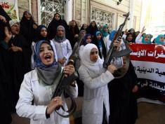 """Iraqi Shiite women hold their weapons as they gather to show their willingness to join Iraqi security forces in the fight against Jihadist militants who have taken over several northern Iraqi cities, on June 18, 2014 in the southern Shiite Muslim shrine city of Najaf. Iraq's premier vowed today to """"face terrorism"""" and insisted security forces had suffered a """"setback"""" rather than defeat, as militants pressing a major offensive attacked the country's largest oil refinery. AFP PHOTO/HAIDAR HAMDANI        (Photo credit should read HAIDAR HAMDANI/AFP/Getty Images)"""