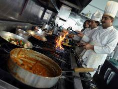 """ISLAMABAD, PAKISTAN:  Pakistani cooks prepare dishes in the kitchen of Cafe Lazeez restaurant, a British curry chain, in Islamabad, 02 March 2005.  Cafe Lazeez owner Zahid Kasim, who launched the first of his Cafe Lazeez eateries in London 13 years ago and helped to update the country's ubiquitous """"Indian"""" restaurants from relics of the 1970s to trendy culinary experiences, has gambled that he can successfully export his fusion of South Asian and European cuisine the 6,000 kilometers (3,728 miles) back to Islamabad, the capital of his food-crazy native country.   AFP PHOTO/Farooq NAEEM  (Photo credit should read FAROOQ NAEEM/AFP/Getty Images)"""