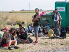 SZEGED, HUNGARY - AUGUST 13:  Migrants who have just crossed the border from Serbia into Hungary wait for a bus organised by the police to take them to the nearby Roszke transit centre. Fot. Matt Cardy/Getty Images