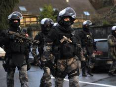 Members of the GIPN and RAID, French police special forces, walk in Corcy, northern France, on January 8, 2015 as they carry out searches as part of an investigation into a deadly attack the day before by armed gunmen on the Paris offices of French satirical weekly Charlie Hebdo. A huge manhunt for two brothers suspected of massacring 12 people in an Islamist attack at a satirical French weekly zeroed in on a northern town on January 8 after the discovery of one of the getaway cars. As thousands of police tightened their net, the country marked a rare national day of mourning for January 7's bloodbath at Charlie Hebdo magazine in Paris, the worst terrorist attack in France for half a century.   AFP PHOTO / FRANCOIS LO PRESTI