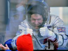 Britain's astronaut Tim Peake gestures to his child from a bus after his space suit was tested at the Russian-leased Baikonur cosmodrome, prior to blasting off to the International Space Station (ISS), on December 15, 2015. Russia's Soyuz TMA-19M spacecraft carrying the International Space Station (ISS) Expedition 46/47 crew of Britain's astronaut Tim Peake, Russian cosmonaut Yuri Malenchenko and US astronaut Tim Kopra is scheduled to blast off to the ISS on December 15, 2015. AFP PHOTO / KIRILL KUDRYAVTSEV / AFP / KIRILL KUDRYAVTSEV        (Photo credit should read KIRILL KUDRYAVTSEV/AFP/Getty Images)