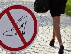 A woman wearing high-heel-shoes, walks past a sign forbidding those shoes, along a coble-stoned pathway leading to the offices of German pharmaceutical company Boehringer Ingelheim in the western German city of Ingelheim on April 20, 2010.  AFP PHOTO DDP /  TORSTEN SILZ GERMANY OUT (Photo credit should read TORSTEN SILZ/AFP/Getty Images)