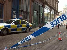 BELFAST, UNITED KINGDOM:  A police line tapes off the side of the Northern Bank main branch on Wellington Street in Belfast 21 December 2004, were robbers have stolen millions of pounds after holding two members of staff hostage. Bank robbers have fled with several million pounds after two bank employees were taken hostage in Northern Ireland's capital Belfast, security sources said today. The robbers went into a branch of the Northern Bank on Wellington Street after holding two members of staff hostage in their homes, said the sources, quoted by Britain's domestic Press Association news agency. AFP PHOTO/Peter MUHLY  (Photo credit should read PETER MUHLY/AFP/Getty Images)