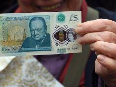 A woman holds up a new £5 (6.5 euros, $7.2) banknote bearing the image of wartime leader Winston Churchill at its unveiling by the Bank of England at Blenheim Palace in Woodstock on June 2, 2016.    The note, to be rolled out from September, is the first to be printed on polymer -- a thin, flexible plastic film that is seen as more durable and secure and is already used in Australia and Canada. / AFP / POOL / Joe Giddens        (Photo credit should read JOE GIDDENS/AFP/Getty Images)