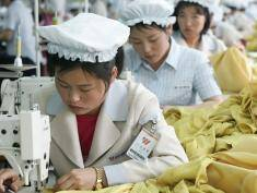 KAESONG, NORTH KOREA - MAY 22: North Korean women work at the assembly line of the factory of South Korean textile company ShinWon at the Kaesong industrial complex on May 22, 2007 in Kaesong, North Korea. 300 South Korean companies, mostly labour-intensive manufacturers, are waiting to build their factories on the site by the end of 2007, just 10 km north of the world's most heavily fortified border bisecting the two Koreas. They plan to hire more than 100,000 North Koreans to make products ranging from shoes and watches, clothes, according to officials from Kaesong industrial complex. About 2,000 South Korean companies have applied to move their production facilities into the Kaesong complex, where they can pay only one-thirtieth of the monthly wage per worker they pay at home or half the pay even in China. (Photo by Chung Sung-Jun/Getty Images)