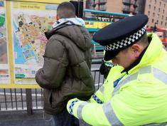 """Police officers, combating potential knife-crime, stop and search people arriving in Liverpool by bus for traditional celebrations ahead of the festive period, 21 December, 2007, Liverpool, England.  The last working day  of the pre Christmas week is dubbed """"Mad Friday"""" locally, giving the police their busiest night of the year as revelers flock to the city's bars, pubs and clubs to kick off the holidays."""