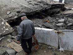 A resident negotiates a destroyed overpass in the Oktyabrsky district close to Donetsk's international airport in the self-proclaimed Donetsk People's Republic (DNR) on March 14, 2015. The area, destroyed over months of artillery exchanges, is still sporadically under mortar and small arms fire.  AFP PHOTO / JOHN MACDOUGALL        (Photo credit should read JOHN MACDOUGALL/AFP/Getty Images)