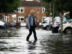 LONDON, ENGLAND - JUNE 23:  A woman steps through water as she crosses a flooded street on June 23, 2016 in Battersea, London, England. Parts of the capital and the South East suffered travel disruption and floods following overnight thunderstorms. (Photo by Carl Court/Getty Images)