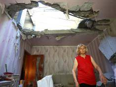 TOPSHOT - A resident of the eastern Ukrainian city of Donetsk walks through her apartment building that was destroyed as a result of night shelling between Ukrainian forces and pro-Russian separatists on June 24, 2016. / AFP / Aleksey Filippov        (Photo credit should read ALEKSEY FILIPPOV/AFP/Getty Images)