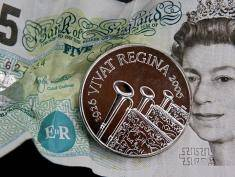London, UNITED KINGDOM:  A commemorative five pound coin is unveiled by the Royal Mint in London, 21 March 2006, as a celebration of Britain's Queen Elizabeth II's 80th birthday year. Designed by artist Danuta Solowiej-Wedderburn, the coin has ceremonial trumpets with banners as a salute to the Queen. AFP PHOTO/BEN STANSALL  (Photo credit should read BEN STANSALL/AFP/Getty Images)