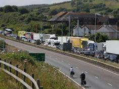 """Traffic stands stationary in a traffic jam with travellers resting outside their vehicles on the main road leading into the port of Dover on the south coast of England on July 24, 2016. British officials were drafted in to help French border police on Sunday after 15-hour queues built up at the port of Dover due to heightened entry checks. The local Kent Police force said there was a 12-mile tailback, which it put down to a """"vast volume of holiday traffic"""". / AFP / DANIEL LEAL-OLIVAS        (Photo credit should read DANIEL LEAL-OLIVAS/AFP/Getty Images)"""