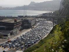 """Lines of traffic queue to enter the port of Dover on the south coast of England on July 24, 2016. British officials were drafted in to help French border police on Sunday after 15-hour queues built up at the port of Dover due to heightened entry checks. The local Kent Police force said there was a 12-mile tailback, which it put down to a """"vast volume of holiday traffic"""". / AFP / DANIEL LEAL-OLIVAS        (Photo credit should read DANIEL LEAL-OLIVAS/AFP/Getty Images)"""
