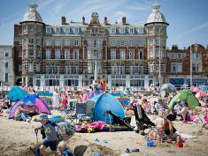WEYMOUTH, ENGLAND - JULY 30:  People gather on the beach as they enjoy the warm weather on the seafront on July 30, 2014 in Weymouth, England. Figures released by the Met Office show that this July is likely to go down as one of the warmest and sunniest on record. However the arrival of August will also see the return of more unsettled weather with the potential for heavy rain at the weekend.  (Photo by Matt Cardy/Getty Images)