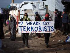 CALAIS, FRANCE - FEBRUARY 29:  Migrants carry a placard as part of the 'jungle' migrant camp is cleared on February 29, 2016 in Calais, France  The French authorities have begun dismantling part of the migrant encampment in the northern French town of Calais and relocating people to purpose-built accommodation nearby.  (Photo by Carl Court/Getty Images)