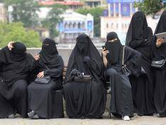 Foreign tourists wearing niqab have a rest on a bench in downtown Tbilisi on August 16, 2016.  / AFP / Vano Shlamov        (Photo credit should read VANO SHLAMOV/AFP/Getty Images)