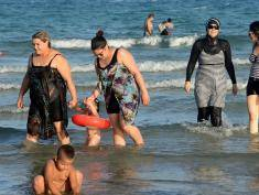 "Tunisian women, one (2ndR) wearing a ""burkini"", a full-body swimsuit designed for Muslim women, walk in the water on August 16, 2016 at Ghar El Melh beach near Bizerte, north-east of the capital Tunis.  / AFP / FETHI BELAID        (Photo credit should read FETHI BELAID/AFP/Getty Images)"