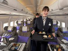 A flight attendant for the new airline Open Skies, a 100 percent business class airline with authentic French cuisine, poses on March 24, 2010 at Washington-Dulles International airport in Virginia. The upscale airline travels from New York and Washington, DC to Paris. AFP Photo/Paul J. Richards (Photo credit should read PAUL J. RICHARDS/AFP/Getty Images)