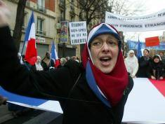 "PARIS - JANUARY 17:  A Muslim woman demonstrates in the street against the French proposal to bar Muslim women from wearing headscarves in state schools on January 17, 2004 in Paris, France. French President Jacques Chirac asked parliament to ban the wearing of ""hijab"" (head scarf in Arabic). Other conspicuous religious symbols such as Jewish skullcaps and large crosses also face a ban in public schools to protect the country's secular nature. (Photo by Pascal Le Segretain/Getty Images)"