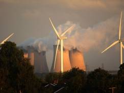 Recently installed wind turbines generate electricty in the shadow of Drax, Europe's biggest coal fired power station, on August 24, 2010 in Selby, England. Thr Rusholme wind farm will create 24 Mega Watts when fully operational in comparison to Drax which creates 3,960 Mega Watts.