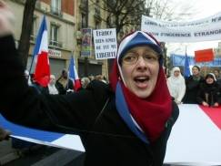 """PARIS - JANUARY 17:  A Muslim woman demonstrates in the street against the French proposal to bar Muslim women from wearing headscarves in state schools on January 17, 2004 in Paris, France. French President Jacques Chirac asked parliament to ban the wearing of """"hijab"""" (head scarf in Arabic). Other conspicuous religious symbols such as Jewish skullcaps and large crosses also face a ban in public schools to protect the country's secular nature. (Photo by Pascal Le Segretain/Getty Images)"""