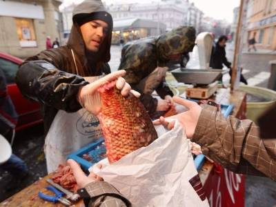 PRAGUE, CZECH REPUBLIC - DECEMBER 23:  A fishmonger drops a Christmas carp filet into a customer's shopping bag at his stall on December 23, 2009 in Prague, Czech Republic. Deep-fried carp with potato salad preceded by carp tripe soup is the traditional Czech Christmas dinner, and in the days before fisheries from southern Bohemia, where carp farming goes back hundreds of years, sell the live fish from big tubs on street corners.  (Photo by Sean Gallup/Getty Images)